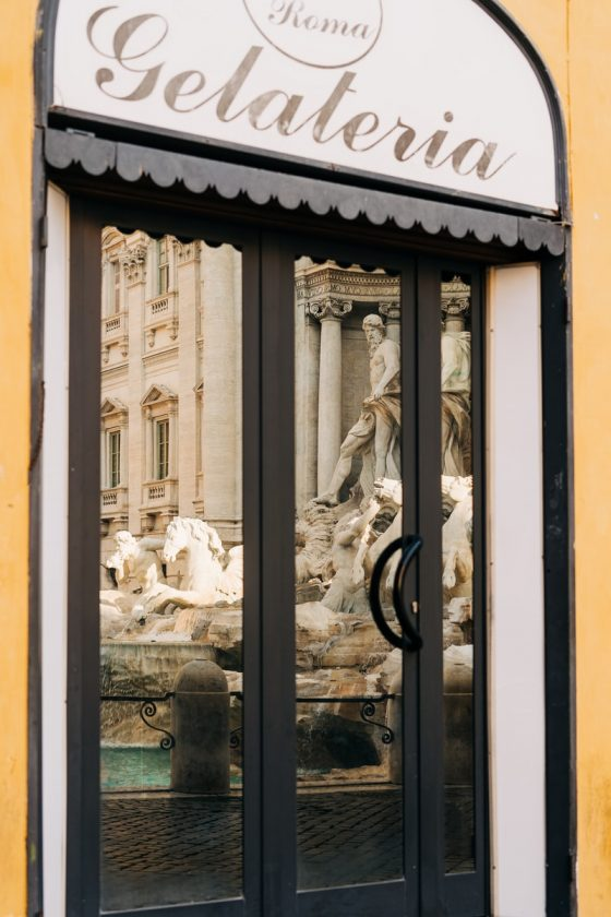 The Trevi Fountain reflected in the window of a gelateria in Rome, Italy