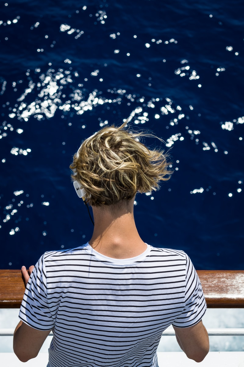 woman wearing white and black striped shirt looking at water